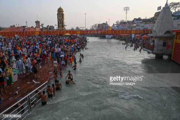 Hindu devotees take a holy dip in the waters of the River Ganges on the eve of Shahi Snan on Maha Shivratri festival during the ongoing religious...