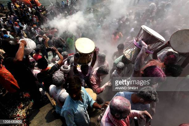 Hindu devotees throw ashes as they celebrate Holi, the spring festival of colours, during a traditional gathering at Manikarnika cremation ghat in...
