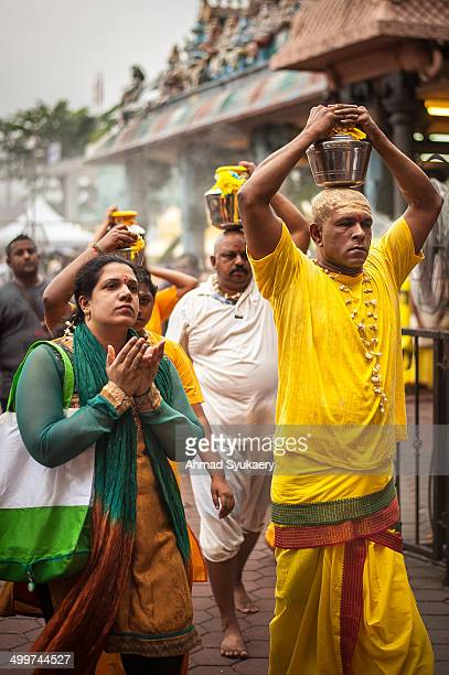 CONTENT] Hindu devotees walking to Batu Caves Temple Kuala Lumpur while carrying a pot of milk on their head as part of Thaipusam ritual