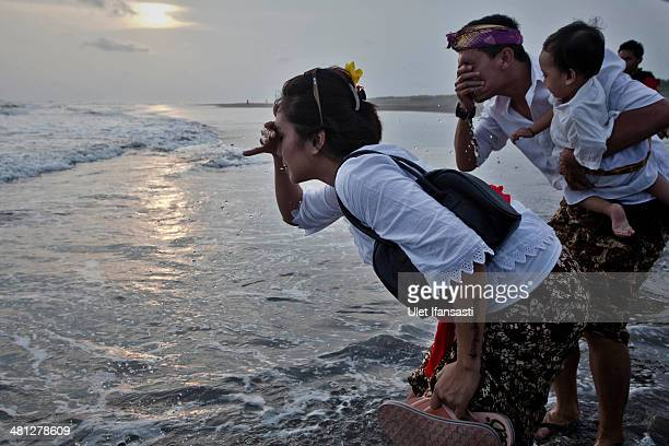 Hindu devotees wash their faces with sea water as they pray during the Melasti ritual ceremony at Parangkusumo beach on March 28 2014 in Yogyakarta...