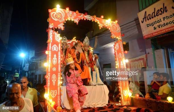 Hindu devotees watch a religious procession as young Indian artists sit on chariot while on the way to perfrom a traditional Ramleela drama which...
