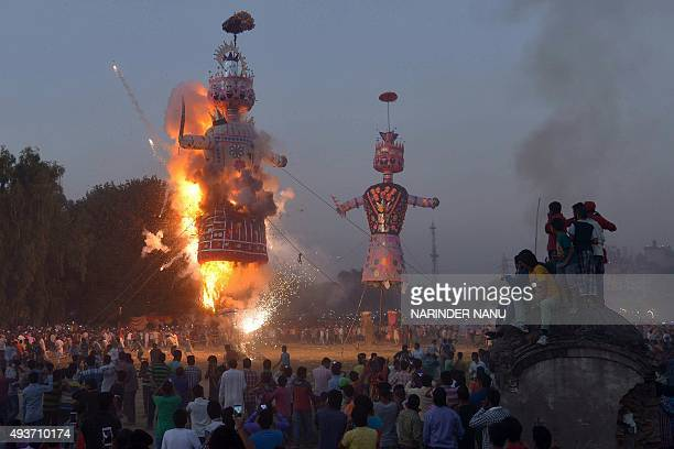 Hindu devotees watch an effigy of the Hindu demon king Ravana stuffed with firecrackers burn at the grounds in Amritsar on October 22 on the occasion...