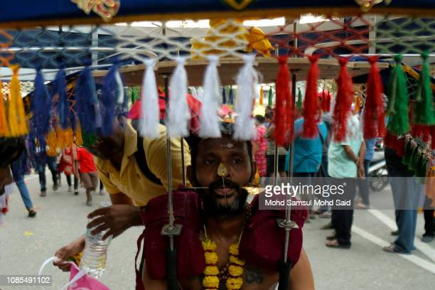 Hindu devotees with a piercing through his mouth carries a kavadi as he rest for their pilgrimage to the sacred Batu Caves temple during Thaipusam...