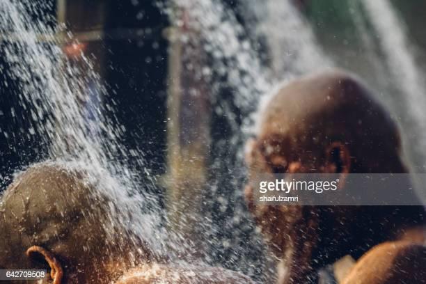 hindu devotes take a shower during thaipusam festival in batu caves, kuala lumpur, malaysia - shaifulzamri stock-fotos und bilder