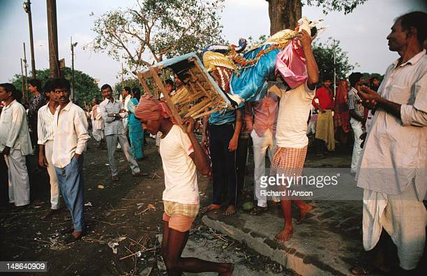 a hindu diety being carried to the hooghly river for immersion during the festival of dussehra, known as durga puja in west bengal - hooghly river stock pictures, royalty-free photos & images
