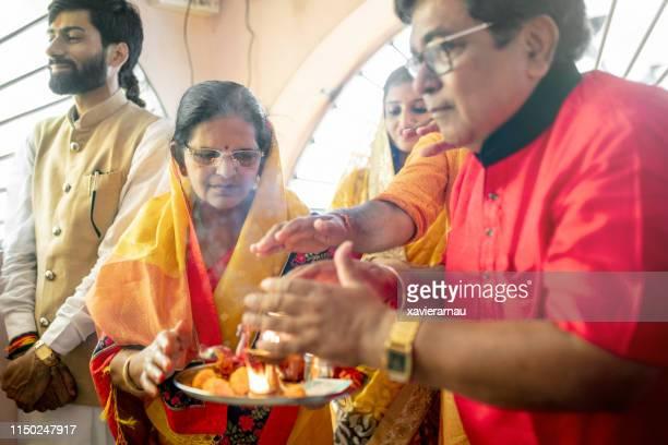 hinduisk familj tar värme av diya efter bön - hinduism bildbanksfoton och bilder