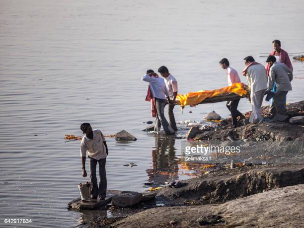 hindu funeral by ganges river varanasi,india - ganges river dead bodies stock photos and pictures