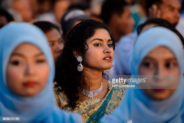 A Hindu girl and Muslim girls take part in an Interreligious Gathering of Prayer for Peace ceremony in Yangon on October 31 2017 The gathering is to...