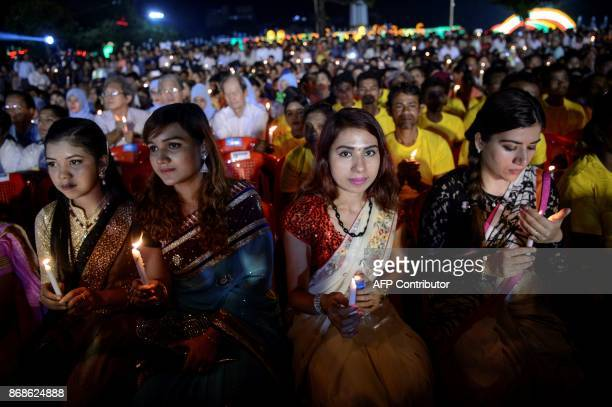 Hindu girls hold candles as they take part in an Interreligious Gathering of Prayer for Peace ceremony in Yangon on October 31 2017 The gathering is...