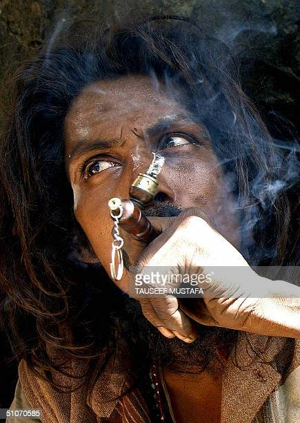 Hindu hermit smokes a pipe in the village of Chandanwari some 114kms south of Srinagar.15 July 2004. Some 1,000 Hindu pilgrims set out on a risky...