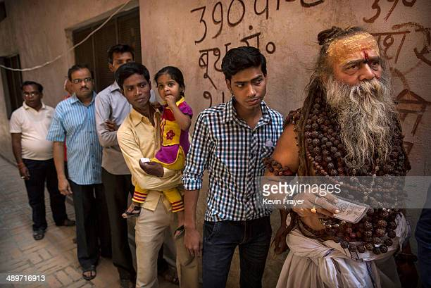 Hindu holy man or Sadhu holds his election card as he waits in line to vote with others at a polling station on May 12 2014 in Varanasi India Indians...