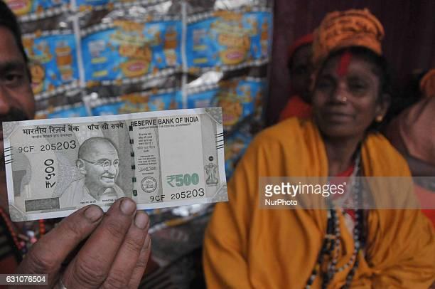A Hindu holy man or sadhu showing New 500 Rupee at the temporary Gangasagar Mela Camp during the MAKARSANKANTRI festival in KolkataWest Bengal India...