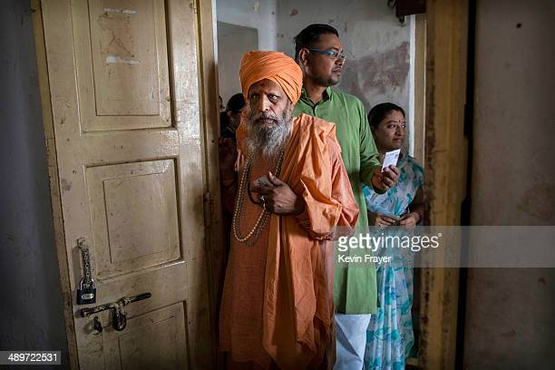 Hindu holy man or Sahu holds his voting card as he waits in line to vote at a polling station on May 12 2014 in Varanasi India Indians voted in the...