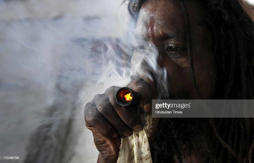 A Hindu holy man smokes chillum as he waits to register for the annual pilgrimage to the Amarnath cave shrine on July 2, 2013 in Jammu, India. Thousands of pilgrims annually visit the remote Himalayan shrine of Amarnath at 3,888 meters (12,756 feet) above sea level to worship an icy stalagmite representing Shiva, the Hindu god of destruction. A small batch of 1,785 devotees today left Jammu base camp for the Amarnath cave shrine. The sixth batch, including 1,395 male, 326 women and 14 children, apart from 50 sadhus, was on its way to twin base camps of Pahalagam and Baltal in Kashmir Valley. Over 50,000 pilgrims have paid obeisance at the cave shrine of Amarnath in south Kashmir till last evening.