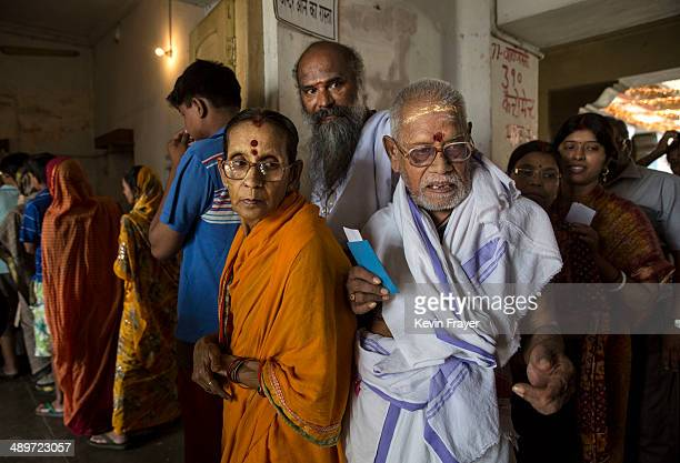 Hindu holy men and women mark their names before voting at a polling station on May 12 2014 in Varanasi India Indians voted in the ninth and final...
