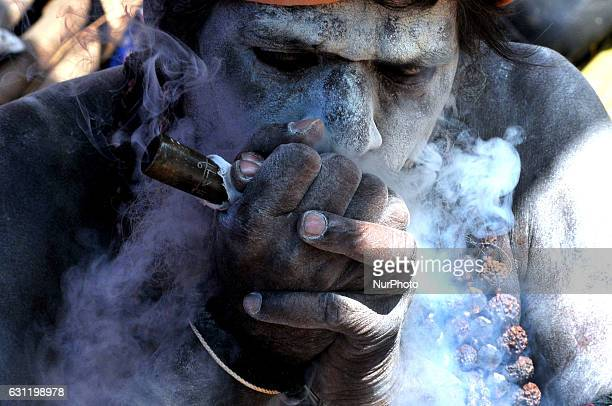 A Hindu holy Naga sadhu smokes marijuana on a chillum at the temporary Gangasagar Mela Camp during the MAKARSANKANTRI festival in KolkataWest Bengal...