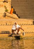 traditonal hindu indian man worshipping ganges