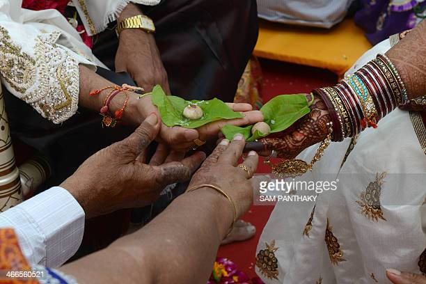 A Hindu Jain bridal couple participate in a ritual during the 32nd Jain Samuh Lagnotsav or 32nd Jain Mass Wedding Ceremony at the Karnawati Club in...