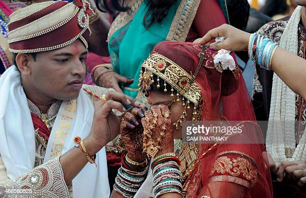 A Hindu Jain groom assists his bride as the 'Mangal Sutra' 'Holy Auspicious Thread' is entangled during the 32nd Jain Samuh Lagnotsav or 32nd Jain...