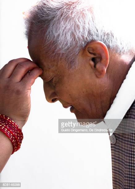 a hindu man receives a tika on his forehead during bhai tika (tihar, diwali) celebrations in kathmandu, nepal. - bhai phonta stock photos and pictures