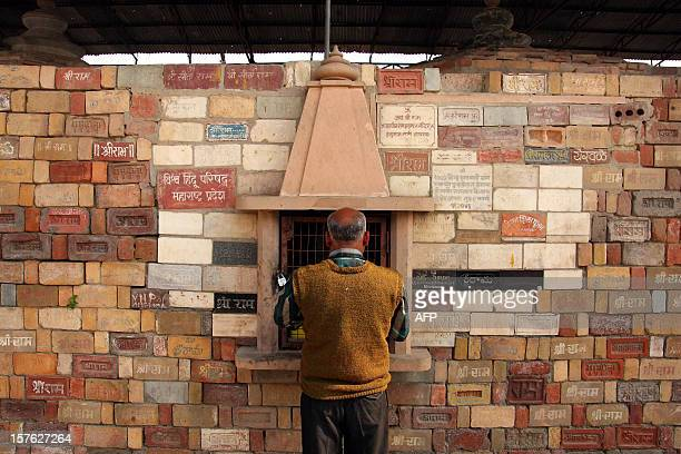A Hindu man stands at a wall of bricks bearing the name of 'Shri Ram' at the Karsevak Puram workshop in Ayodhya on December 5 the eve of the 20th...