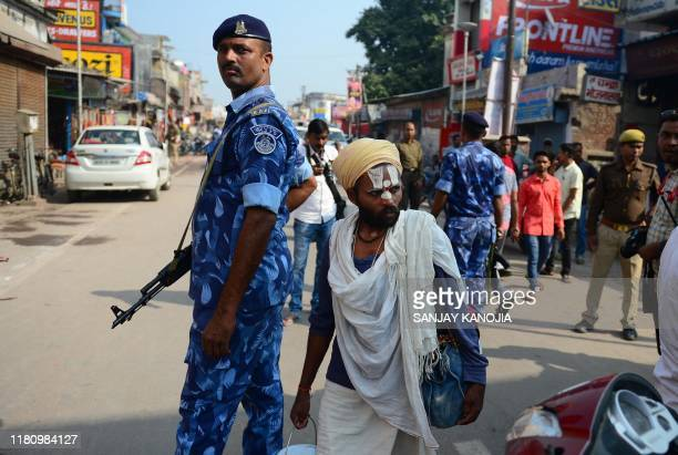A Hindu man walks past security personnel on a road in Ayodhya on November 9 ahead of a Supreme Court verdict on the disputed religious site India...
