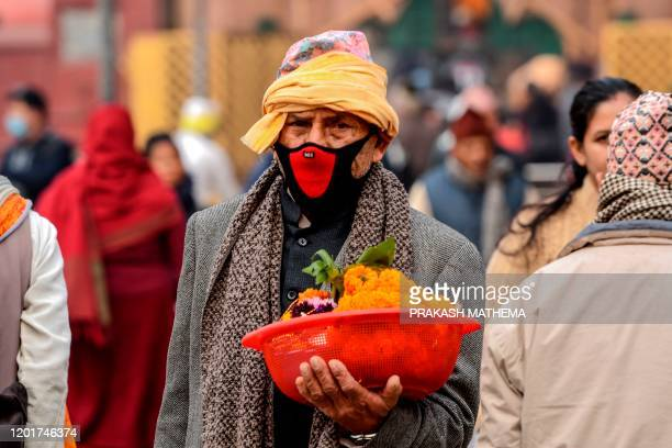 Hindu man wearing a protective facemask carries a bucket filled with offerings ahead of Hindu festival 'Maha Shivaratri' in Kathmandu on February 19,...