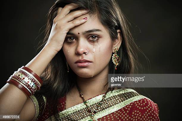 Hindu married woman crying with tears and looking at camera.