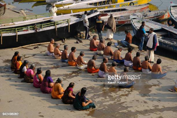Hindu men and women sitting in small rows attend a religious ceremony for their dead parents performed by a priest by the Ganga River banks on...