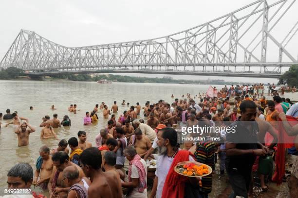 Hindu men seen offering food and water to ancestors on the bank of river Hooghly at Jagannath Ghat on September 19 2017 in Kolkata India As per Hindu...