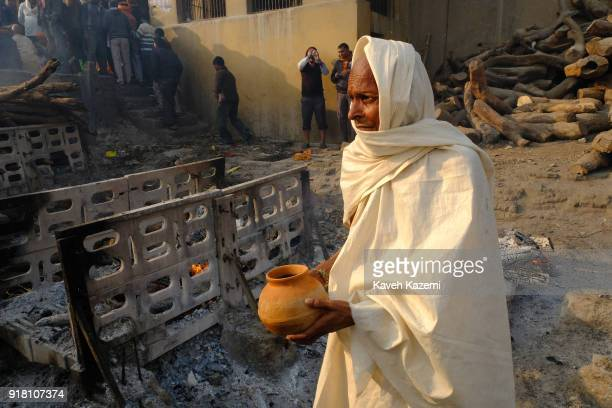 Hindu monk carries a bowl of water to pour over the ashes of a dead man after the act of cremation is completed in Manikarnika Ghat on January 28,...