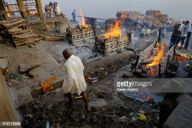 Hindu monk walks past burning pyres seen during cremation ceremonies in Manikarnika Ghat on January 28, 2018 in Varanasi, India. Manikarnika Ghat is...