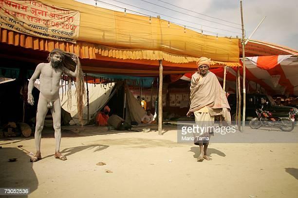 Hindu Naga Sadhu adjusts his hair as a pilgrim walks past near the ritual bathing site at Sangam the confluence of the Ganges Yamuna and mythical...