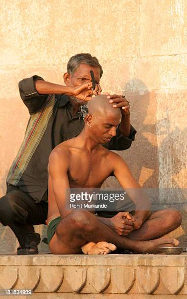 Hindu pilgrim from Uttar Pradesh is getting his head shaved on the Harishchandra Ghat on the banks of the river Ganga in Varanasi, after the...