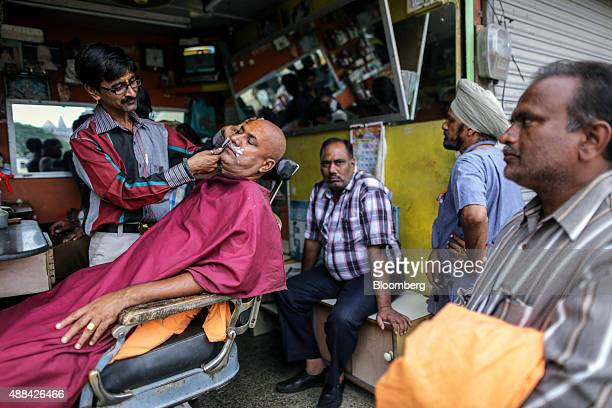 A Hindu pilgrim has a shave at a barber's store in Trimbakeshwar Maharashtra India on Friday Sept 11 2015 Millions of pilgrims in a landscape awash...