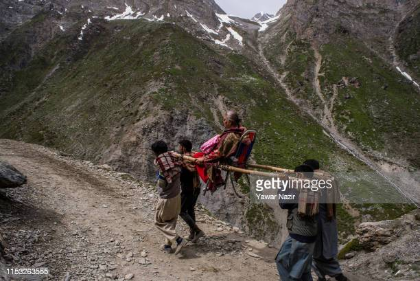 Hindu pilgrim is carried by Kashmiri Muslim palanquin bearers as she makes his pilgrimage to the sacred Amarnath Caves one of the most revered of...