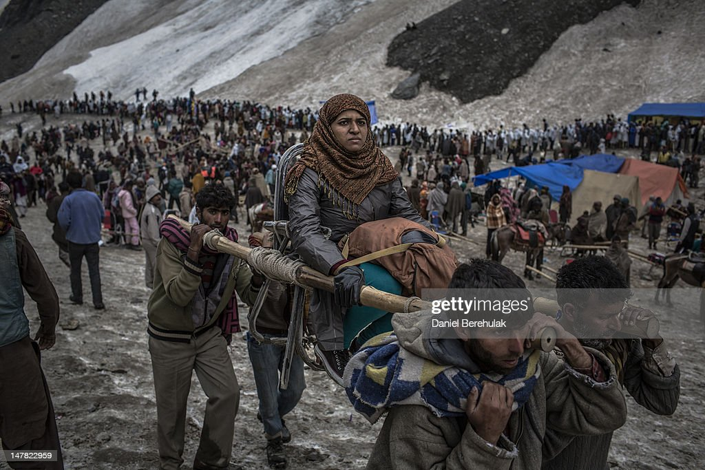 A Hindu pilgrim is carried on a palanquin by Kashmiri bearers over a glacier on her way to the sacred Amarnath Cave, one of the most revered Hindu shrines, on June 29, 2012 near Baltal, Kashmir, India. Hindu devotees brave sub-zero temperatures to hike over glaciers and high altitude mountain passes to reach the sacred Amarnath cave, which houses an ice stalagmite, a stylized phallus, worshiped by Hindus as a symbol of the god Shiva. More than 700,000 Hindu pilgrims are expected to take part in this year's two-month pilgrimage, according to local officials, causing strain on the environment and political stability of the region, which has long fought for independence from India.