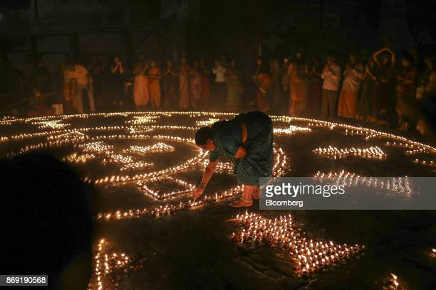 A Hindu pilgrim lights an oil lamp during a religious ceremony on the banks of the Ganges river in Varanasi Uttar Pradesh India on Saturday Oct 29...