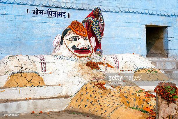 Hindu pilgrim making offerings to Bhishma Pitamah The statue is made of mud on the banks of the Ganges Varanasi Uttar Pradesh India Bhishma was a...