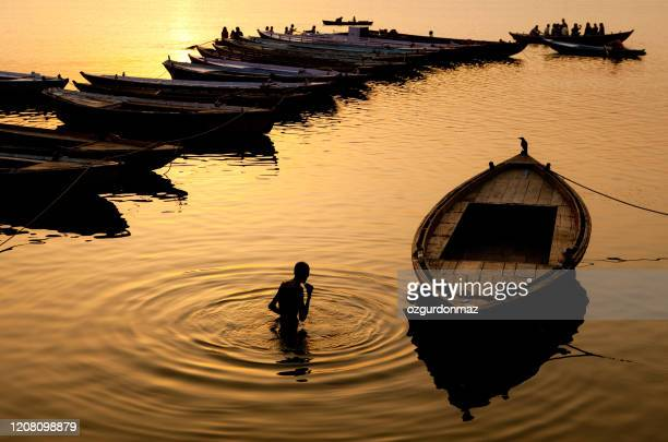hindu pilgrim offers prayers in the river ganges in varanasi, india - pilgrimage stock pictures, royalty-free photos & images