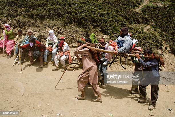 Hindu pilgrim on a Dandi Chair on the Amarnath Cave trail, while other pilgrims are resting on the side of the trail. Local Muslim Kashmiri provide...