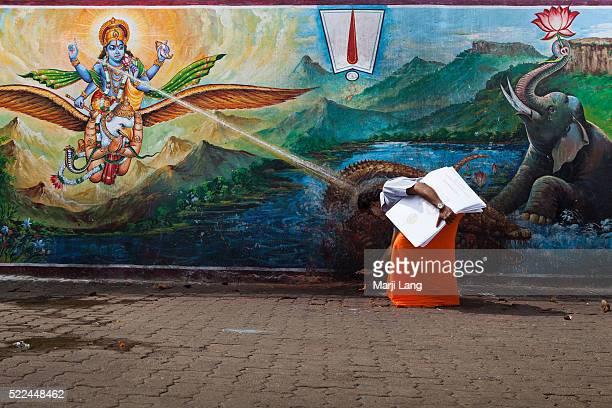 Hindu pilgrim praying at Sri Venkateswara swami temple in Tirumala Andhra Pradesh India The pilgrim seems to be blessed by a ray of light from the...