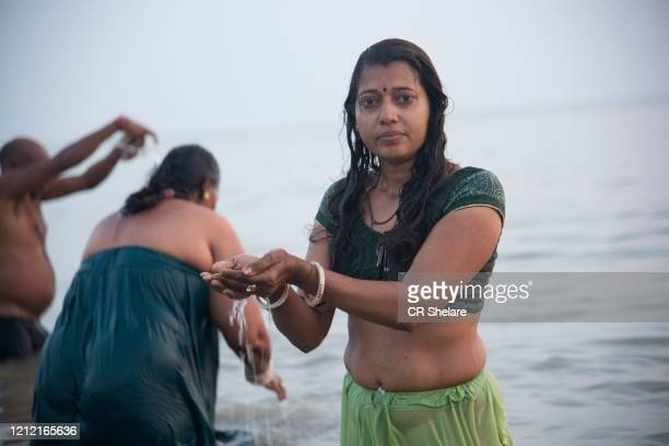 hindu pilgrim takes a holy dip in ganges at gangasagar islands, india. - makar sankranti stock pictures, royalty-free photos & images