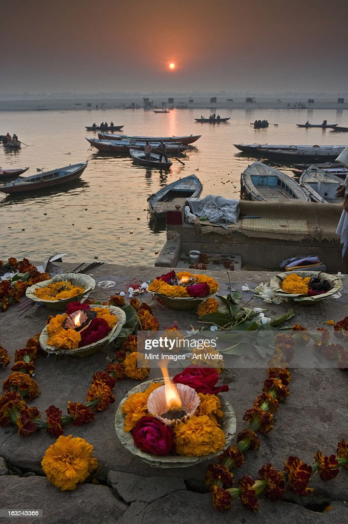 Hindu pilgrims come to Varanasi on the River Ganges to make offerings at the ghats, and swim in the sacred waters. : Stock Photo