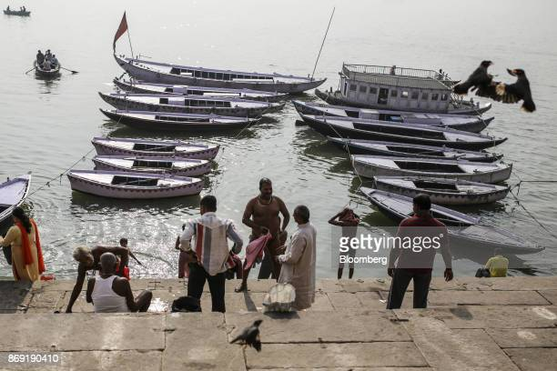 Hindu pilgrims gather as boats sit docked on the banks of the Ganges river in Varanasi Uttar Pradesh India on Saturday Oct 29 2017 A big drop in...
