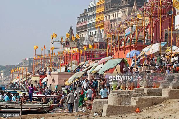 Hindu pilgrims gathering at a ghat to bathe in the Ganges river in Varanasi Uttar Pradesh India