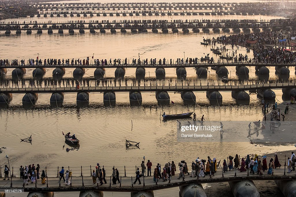 Hindu pilgrims make their way over pontoon bridges near Sangam, the confluence of the holy rivers Ganges, Yamuna and the mythical Saraswati, during the Maha Kumbh Mela on February 9, 2013 in Allahabad, India. The Maha Kumbh Mela, believed to be the largest religious gathering on earth is held every 12 years on the banks of Sangam, the confluence of the holy rivers Ganga, Yamuna and the mythical Saraswati. The Kumbh Mela alternates between the cities of Nasik, Allahabad, Ujjain and Haridwar every three years. The Maha Kumbh Mela celebrated at the holy site of Sangam in Allahabad, is the largest and holiest, celebrated over 55 days, it is expected to attract over 100 million people.