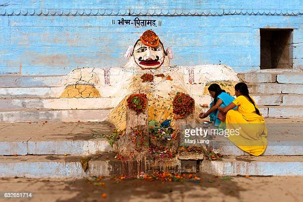 Hindu pilgrims making offerings to Bhishma Pitamah The statue is made of mud on the banks of the Ganges Varanasi Uttar Pradesh India Bhishma was a...