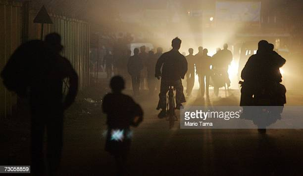 Hindu pilgrims move along a street at night near the ritual bathing site at Sangam the confluence of the Ganges Yamuna and mythical Saraswati rivers...