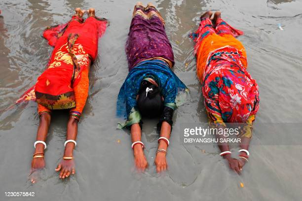 Hindu pilgrims offer prayers at the confluence of Ganges and the Bay of Bengal during the Gangasagar Mela on the occasion of Makar Sankranti, a day...